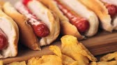 gorąco : Grilled hot dogs on a white hot dog buns with chips and baked beans on the side. Wideo