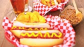 gorąco : Grilled hot dogs with mustard and ketchup on the table with draft beer.
