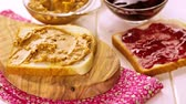 масло : Homemade peanut butter and jelly sandwich on white bread.