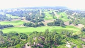 ассортимент : Aerial view of golf course surrounded by natural park.