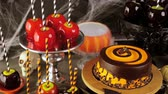food : Table with colored candy apples and cake for Halloween party. Stock Footage