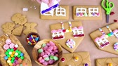 telhados : Decorating gingerbread house with royal icing and colorful candies.