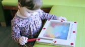 nemluvně : Cute toddler girl drawing with color pencils.