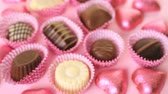 romance : Assorted chocolates on pink background.