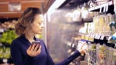 suíça : Young woman shopping in the fresh produce section at the grocery store. Stock Footage
