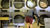 çamaşırhane : Teenage boy doing the laundry in a public self service laundry Stok Video