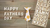 Unfinished wood letters sign Happy Fathers Day on a painted wood background. Stok Video