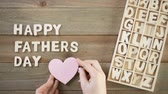 gündüz : Unfinished wood letters sign Happy Fathers Day on a painted wood background. Stok Video