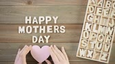 Unfinished wood letters sign Happy Mothers Day on a painted wood background.