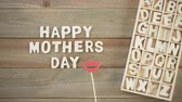 gündüz : Unfinished wood letters sign Happy Mothers Day on a painted wood background.