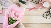 gündüz : Step by step. Florist wrapping pink tulips in bouquet.