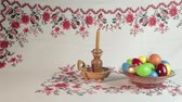освещенный : Orthodox Easter. On a table covered with a tablecloth with ornaments worth plate with colored eggs. Nearby stands a candle in a candlestick. White background with ornament.