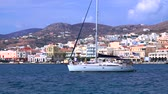 Киклады : White yacht with a crew slowly sails along the embankment of the Mediterranean. Beautiful view of Ermoupolis city on Syros island, Greece. Стоковые видеозаписи