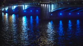 4k handheld tilt up shot of a beautiful historic bridge across the river in a European city at night. A lot of cars with different flashlights are reflected in the water. Kamennoostrovsky bridge, Saint-Petersburg, Russia. Filmati Stock