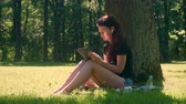 Young woman with wireless headphones uses digital tablet for learning studying and work. Student girl with sunglasses sitting on grass in city park surrounded by trees and foliage at sunny day.