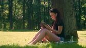 Young woman with wireless headphones pulls out and uses digital tablet for studying and work. Student girl with sunglasses sitting on grass in city park, surrounded by trees and foliage on sunny day.