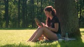 Young woman with wireless headphones using digital tablet for learning, studying and work. Female student girl with sunglasses sits on grass in city park surrounded by trees and foliage at sunny day. Filmati Stock