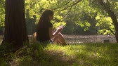Young woman with wireless headphones uses smartphone and digital tablet for learning and work. Student girl with sunglasses sitting on grass in city park surrounded by trees and foliage at sunny day.