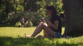 A young pretty woman uses a smartphone and drinks coffee from a paper cup. Student girl sitting on the grass in the shade of a tree in the park among the trees and foliage on a bright sunny day.