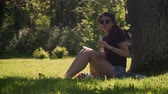 Young beautiful woman in sunglasses uses smartphone, looks into camera and drinks mineral water from plastic bottle. A girl sits on grass in shade of tree in park on bright sunny day.