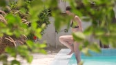 Young caucasian brunette woman in a swimsuit slowly comes out of the pool surrounded by foliage of tropical trees and greenery on a hot sunny day. 4k video.