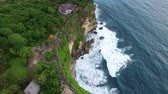 Flight over the Uluwatu temple along the rocky coast in Bali at cloudy day evening. Touristic place. Aerial footage of Bali, Indonesia. Archivo de Video