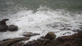 apressando : Large storm waves crashing on rocks in slow motion. Foamy waves hit the volcanic stones of the Andaman Sea shore at stormy cloudy weather. Tropical Island of Koh Samui, Thailand. Stock Footage