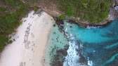 sestup : Frothy waves of clear and colorful turquoise Indian Ocean wash the shore of deserted paradise beach on tropical island. Top view descent aerial footage of secret deserted beach on Nusa Ceningan, Bali.