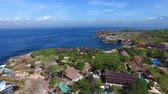záliv : Flying over rocky ledge with luxury villas, swimming pools and country houses. Foamy waves of turquoise Indian Ocean crash against the rocks on bright sunny day. Aerial shot of Nusa Lambongan, Bali. Dostupné videozáznamy