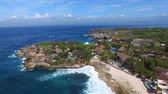 falu : Flying above quiet empty beach of tropical island coastline with villas and country houses surrounded by vegetation. Foamy waves of turquoise ocean wash the sand on a bright sunny day. Aerial.
