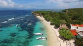 sailboat : Flying high above Mushroom Beach with yellow sand, lush vegetation, luxury villas, resorts and variety of boats and yachts bobbing on foamy waves of turquoise Ocean. Aerial of Nusa Lambongan, Bali.