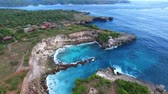 gruta : Flying back of rocky ledges with green vegetation, village houses, hiking paths on top. Grottoes and lagoons washed by waters of turquoise ocean. Foamy waves break on stones. Aerial of Nusa Ceningan. Vídeos