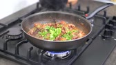 frigideira : Woman drops greens and parsley on stir fried baby octopus with vegetables boiling in a hot frying pan. Cooking seafood dish at home on modern gas stove. 4k 50 frames per second narrow depth of field.