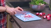 ingredienti : Young woman housewife slicing radish on a blue plastic cutting board. Preparing food ingredients on a stone countertop at a home kitchen. 4k 50 frames per second narrow depth of field close up footage Filmati Stock