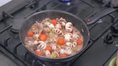 ahtapot : Woman drops fresh cherry tomatoes on fried pan with baby octopus and roasted vegetables. Cooking seafood at home on a modern gas stove. 4k 50 frames per second narrow depth of field close up footage.