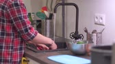ingredienti : Young woman housewife washes vegetables in the kitchen sink and puts them in a steel bowl. Hands wash cucumbers and radishes in the home interior. 4k 50 fps footage narrow depth of field footage.