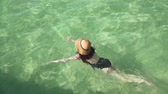 hot water : Young caucasian woman in swimsuit and straw hat swims in clear colorful transparent water near seashore with sandy bottom. Top view of shiny water surface with reflections iridescent rays of light