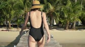 hot water : Young caucasian woman in sunglasses swimsuit and straw hat happily walks on wooden jetty pier towards the beach on tropical island and invites to follow her with a hand. Slow motion follow me footage Stock Footage