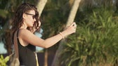 hot water : Pretty young woman in sunglasses and swimsuit takes selfie on beautiful sandy beach by sea. Happy smiling girl pulls her hair, spinning and taking pictures of herself with smartphone. Slow motion.