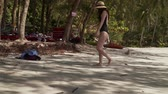 hot water : Young caucasian woman walks along sandy beach by the sea. Girl in swimsuit and straw hat enjoys vacation on paradise tropical island with sandy beach, calm turquoise sea and green trees on the shore. Stock Footage