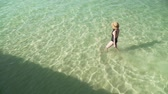 hot water : Young caucasian woman in swimsuit and straw hat enters clear transparent colorful water to swim at seashore with sandy bottom. Top view of shiny water surface iridescent light rays and reflections.