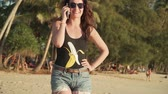 female cell : Pretty young woman in sunglasses and swimsuit makes phone call and talks walking on sandy beach. Happy girl on vacation walks along sea shore of tropical island and calls on smartphone on sunset.