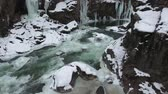 고드름 : Flight over the winter river at the bottom of the gorge. Icicles hang from the stone walls of the gorge.