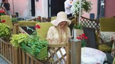 serin : Woman browsing smartphone in outside cafe. Cheerful woman sitting at table in outside restaurant and browsing smartphone. Stok Video