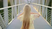 неузнаваемый : Woman throwing up hair on bridge. Back view of blonde woman running on pedestrian bridge and throwing up hair. Стоковые видеозаписи