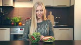 kétség : Girl preferring salad to hamburger. Attractive young woman choosing to eat healthy salad for lunch while sitting at table in stylish kitchen and doing thumbs up gesture and looking at camera. Stock mozgókép