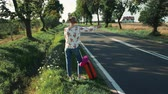 beira da estrada : Young woman hitchhiking on countryside road. Stock Footage