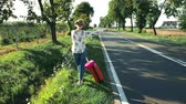 human back : Traveler Girl hitchhiking on a sunny road and walking.