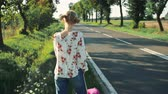 beira da estrada : Young beautiful woman hitchhiking standing on the road with a suitcase. Stock Footage