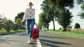 Cheerful Young lady with suitcase walking on road.